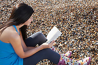 Young woman sitting on beach reading book side view