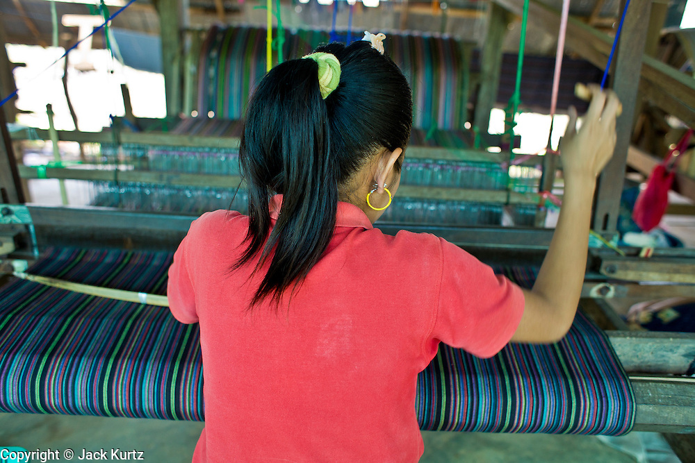"""19 FEBRUARY 2008 -- SANGKLABURI, KANCHANABURI, THAILAND: NGE, a Burmese refugee from the Mon hill tribe, works in the weaving shop at the Baan Unrak Children's Home in Sangklaburi, Thailand. Baan Unrak children's home and school, established in 1991 in Sangklaburi, Thailand, gives destitute children and mothers a home and career training for a better future. Baan Unrak, the """"Home of Joy,"""" provides basic needs to well over 100 children, and  abandoned mothers. The home is funded by donations and the proceeds from the weaving and sewing shops at the home. The home is a few kilometers from the Burmese border. All of the women and children at the home are refugees from political violence and extreme poverty in Burma, most are Karen hill tribe people, the others are Mon hill tribe people. The home was started in 1991 when Didi Devamala went to Sangklaburi to start an agricultural project. An abandoned wife asked Devmala to help her take care of her child. Devmala took the child in and soon other Burmese women approached her looking for help.    Photo by Jack Kurtz"""