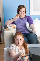 Overweight girl and mother watching television, eating