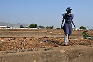 A deminer from Mines Advisory Group (MAG) surveys the rooftop of a former military barracks and weapons store used by northern government forces during Sudan's civil war. The building is next to an open area near the John Garang memorial where Independence ceremonies will be held on July 9th, 2011. The area is heavily contaminated with unexploded ordinance (UXO). The Government of South Sudan asked MAG to help SPLA deminers clear the area before the independance celebrations..Juba, South Sudan. 05/07/2011..Photo © J.B. Russell