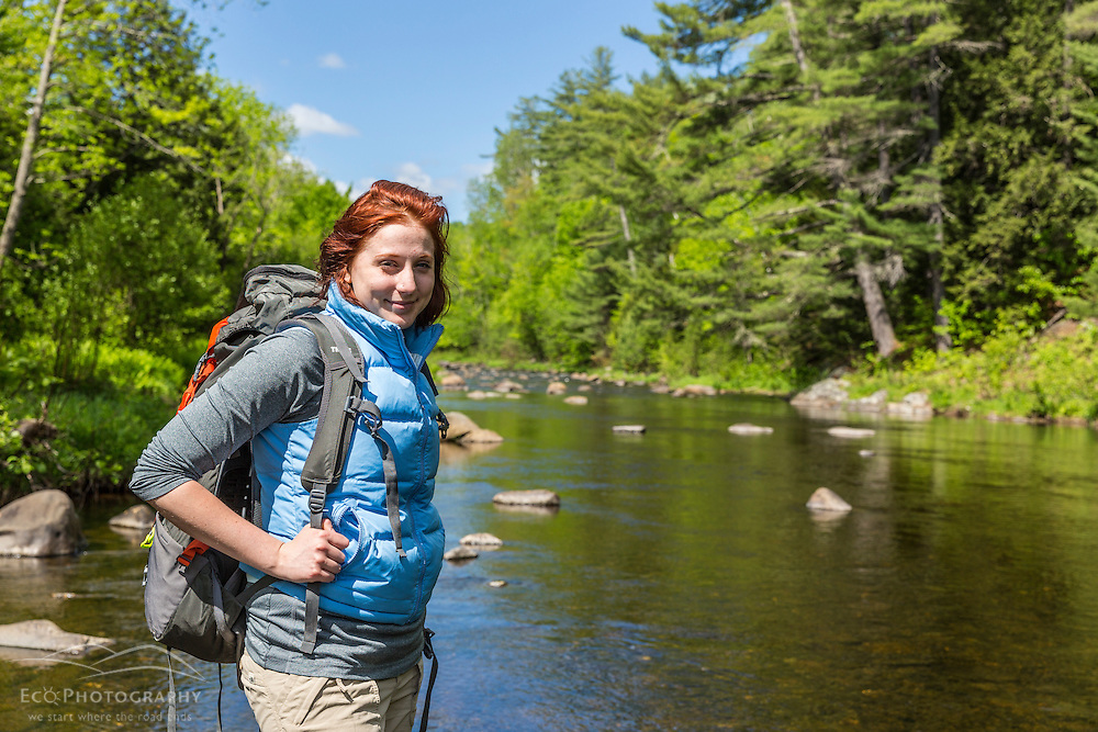 A young woman fords the Pleasant River while hiking on The Appalachian Trail in Maine's 100 Mile Wilderness.