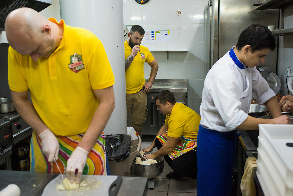 Kirill Deyneka chops onions, left, as Mikhail Yora prepares dough for crusts, bottom, and pizzeria founder Leonid Ostaltsev looks on, center, at Veterano Pizza on January 23, 2016 in Kiev, Ukraine. The three are veterans of the 8th Special Forces Regiment, the 12th Brigade, and the 30th Brigade, respectively. At right is Slava Gerbut, a non-veteran, 18-year old student who prepares the restaurant's Japanese offerings. (Pete Kiehart for The New York Times)