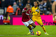 West Ham United midfielder Michail Antonio (30) and Brighton and Hove Albion defender Gaëtan Bong (3) battle over the ball during the Premier League match between West Ham United and Brighton and Hove Albion at the London Stadium, London, England on 2 January 2019.