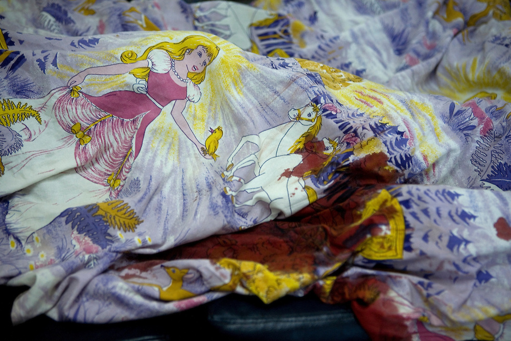 Despite the stitching Mommy continues to bleed. Mommy's bed sheets covered in her blood. Mommy delivered and died from postpartum bleeding at the PCMH (Princess Christian Memorial Hospital). Freetown, Sierra leone.