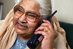 Elderly Asian woman chatting and laughing on the phone,