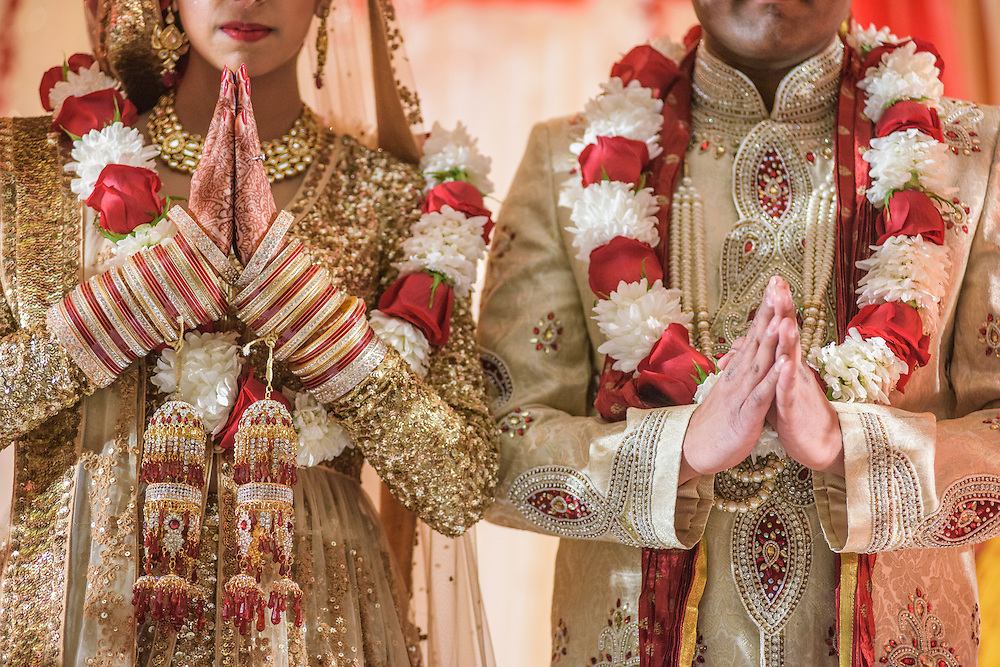 Baltimore, Maryland - December 20, 2014: Trisha Satya Pasricha and Eshwan Ramudu start the wedding ceremony with the Ganesh Puja, a prayer to Lord Ganesh, the god of wisdom, learning, good luck, and the remover of all obstacles in life. Trisha's hands are decorated with henna and her wrists are covered in choorae, traditional wedding bangles.<br /> <br /> The couple, who met at Harvard, during a one of Trisha's student films, were married at the Baltimore Marriott Waterfront Hotel December 20, 2014. <br /> <br /> <br /> CREDIT: Matt Roth for The New York Times<br /> Assignment ID: 30168620A