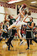 CVU's Sadie Otley (3) leaps over Rice's Stephanie Langlais (10) to take a shot during the girls basketball game between the Rice Green Knights and the Champlain Valley Union Redhawks at CVU High School on Monday night December 14, 2015 in Hinesburg. (BRIAN JENKINS/for the FREE PRESS)