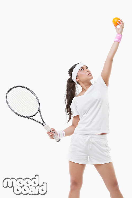 Young female tennis player holding orange and racket against white background