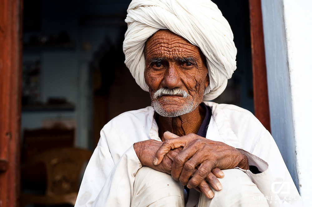 An old man in Udaipur, India watched goings on in the road below from the door of his apartment.