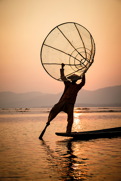 Fisherman catching the final rays of the sun in his net on Lake Inle. They've mastered an unusual technique when it comes to paddling their boats. Carefully balancing on one leg, wrapping their second leg around the oar to guide the vessel through the freshwater lake. The skilled technique means the fishermen can stand and look out for reeds in the water and keep both hands free to handle the cumbersome nets.