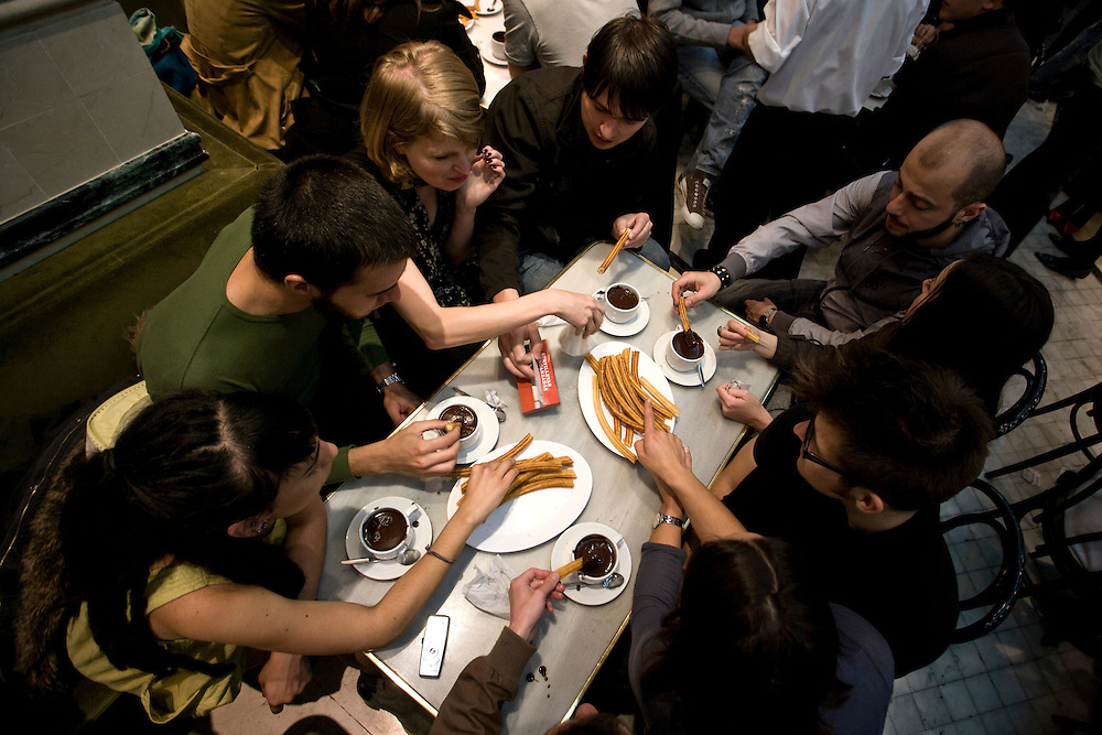 """6:39 AM: A group of young people enjoy traditional Spanish """"chocolate con churros"""" for breakfast at """"San Ginés"""" in Madrid, after a night out partying."""