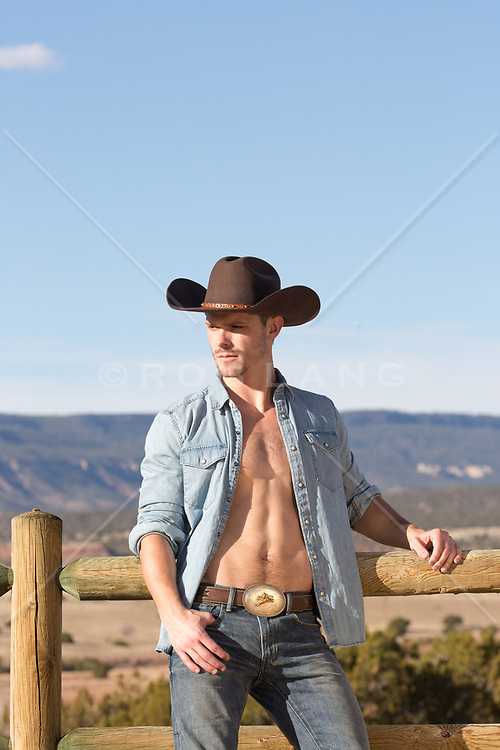 cowboy with an open shirt leaning against a wooden fence