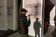 A man speaks into his phone using the speakerphone feature, in a sunny corner next to 'Sketch', a gastro-gallery on Conduit Street, on 20th January 2020, in London, England.