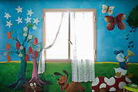 LECCE, ITALY - 10 NOVEMBER 2016: A window is seen here in a room, decorated with cartoon scenes, where female inmates meet their children and where  sommelier classes take place, in the largest penitentiary in the southern Italian region of Apulia, holding 1,004 inmates in the outskirts of Lecce, Italy, on November 10th 2016.<br /> <br /> Here a group of ten high-security female inmates and aspiring sommeliers , some of which are married to mafia mobsters or have been convicted for criminal association (crimes carrying up to to decades of jail time), are taking a course of eight lessons to learn how to taste, choose and serve local wines.<br /> <br /> The classes are part of a wide-ranging educational program to teach inmates new professional skills, as well as help them develop a bond with the region they live in.<br /> <br /> Since the 1970s, Italian norms have been providing for reeducation and a personalized approach to detention. However, the lack of funds to rehabilitate inmates, alongside the chronic overcrowding of Italian prisons, have created a reality of thousands of incarcerated men and women with little to do all day long. Especially those with a serious criminal record, experts said, need dedicated therapy and professionals who can help them.