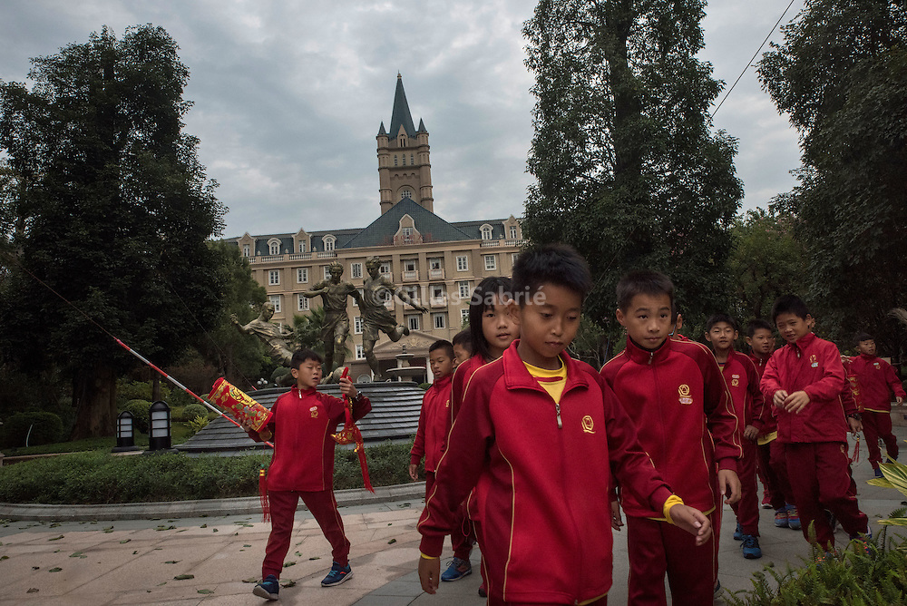 For a story by Chris Buckley, CHINASOCCER<br /> Qingyuan, Guangdong, China, December 6th, 2016<br /> 10 years old students of the Evergrande Football School walking past a statue of football players in the park of the school.<br /> Gilles Sabri&eacute; for The New York Times