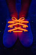 Two shoes tied together with one glowing shoelace. Blacklight photography.