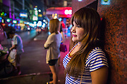 "21 JANUARY 2013 - BANGKOK, THAILAND: A sex worker waits for a client in front of the Nana Entertainment Plaza, a red light district in Bangkok. Prostitution in Thailand is technically illegal, although in practice it is tolerated and partly regulated. Prostitution is practiced openly throughout the country. The number of prostitutes is difficult to determine, estimates vary widely. Since the Vietnam War, Thailand has gained international notoriety among travelers from many countries as a sex tourism destination. One estimate published in 2003 placed the trade at US$ 4.3 billion per year or about three percent of the Thai economy. It has been suggested that at least 10% of tourist dollars may be spent on the sex trade. According to a 2001 report by the World Health Organisation: ""There are between 150,000 and 200,000 sex workers (in Thailand).""   PHOTO BY JACK KURTZ"