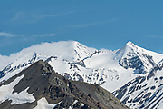 Snow blows on the summit of a mountain in the Alaska Range in Denali National Park Alaska. Denali National Park and Preserve encompasses 6 million acres of Alaska's interior wilderness.