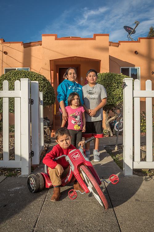 Commercial housekeeper Nereida Apalinar with her kids, Javier (12) and Elizabeth (4) stand behind their next door neighbor, Kevin Vega (4), at the front gate of their home on Washington Street in Calistoga.