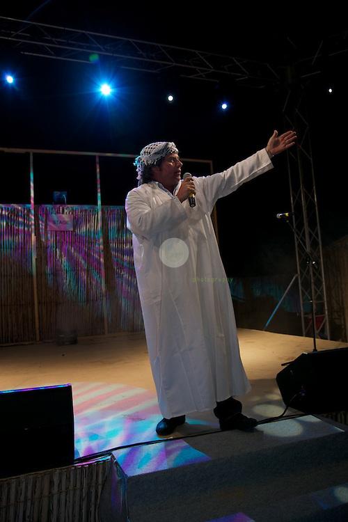 Andy Borg auf der Konzertbuehne im Wuestencamp bei Dubai, gekleidet in einer Kandura, dem Gewand der emiratischen Maenner.