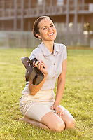 Smiling young businesswoman holding high heels while sitting in office lawn