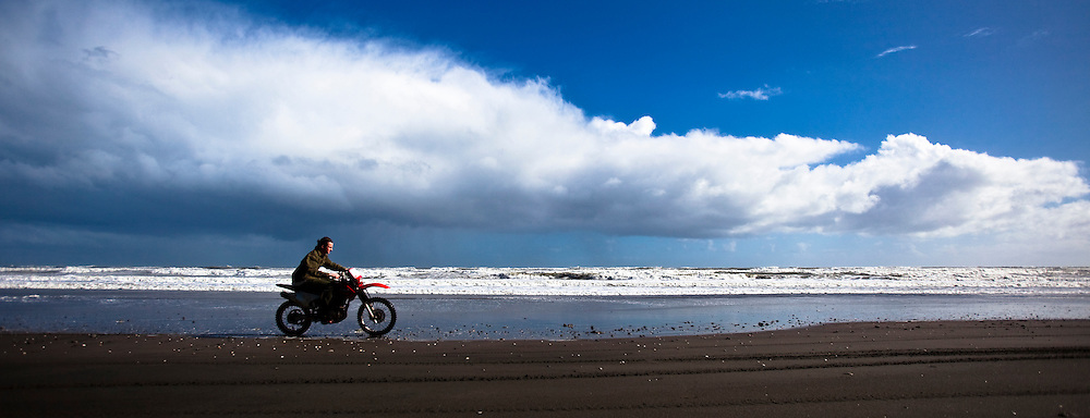Man rides a motorcycle on a black sand beach in New Zealand