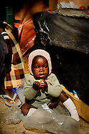a young baby sitting on plastic garbage in Katima Mulilo market, Namibia
