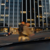 Pedestrians in a crosswalk in the early evening in the Rosslyn section of Arlington, VA