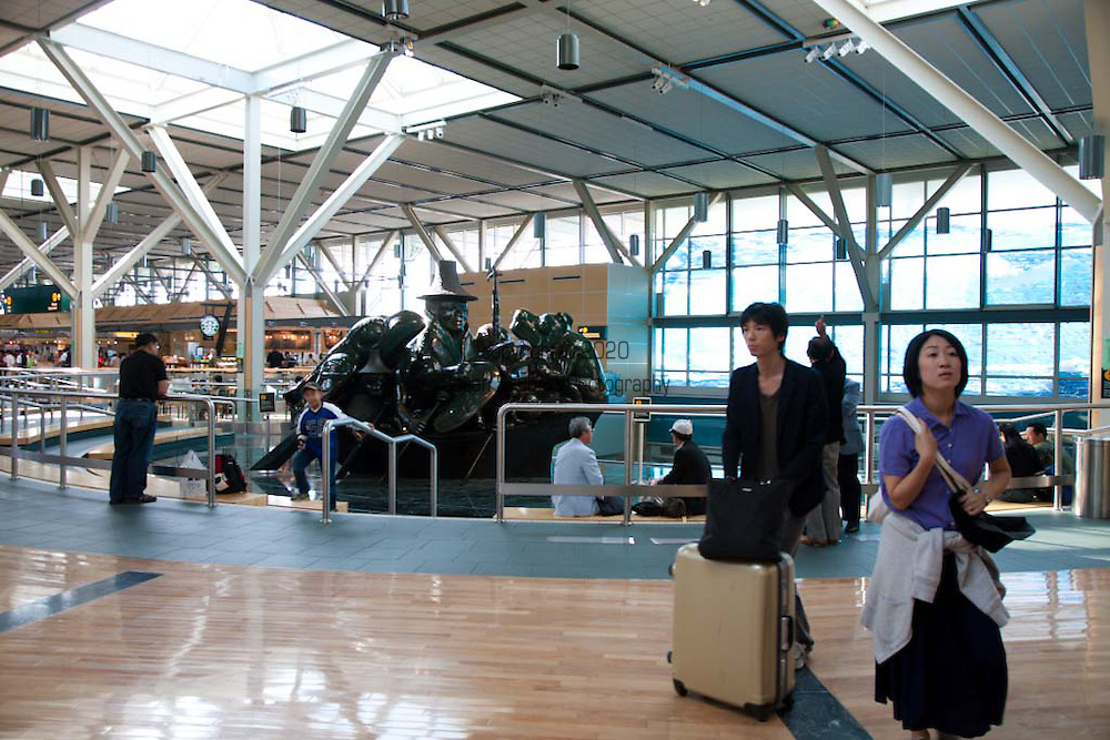 """YVR, Vancouver, B.C. International Airport.  The interior design of the International Terminal was inspired by British Columbia's great outdoors and the art of the Northwest Coast that depicts British Columbia's native wildlife, mountains, rivers, forests, and aboriginal heritage. .The Spirit of Haida Gwaii, The Jade Canoe, by Bill Reid, provides the focal point to the entrance of the International Terminal. The bronze sculpture features legendary Haida creatures paddling a boat that """"goes on, forever anchored in the same place."""""""