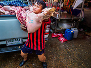 08 JUNE 2017 - BANGKOK, THAILAND: A worker delivers a freshly butchered hog to a meat shop in Khlong Toey Market, Bangkok's main fresh market. Thai consumer confidence dropped for the first time in six months in May following a pair of bombings in Bangkok, low commodity prices paid to farmers and a sharp rise in the value of the Thai Baht versus the US Dollar and the EU Euro. The Baht is surging because of political uncertainty, related to Donald Trump, in the US and Europe. The Baht's rise is being blamed for a drop in Thai exports. This week the Baht has been trading at around 33.90 Baht to $1US, it's highest point in two years.      PHOTO BY JACK KURTZ
