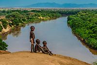 Young Kara tribe boys with the Omo River behind. Dus village, Omo Valley, Ethiopia.