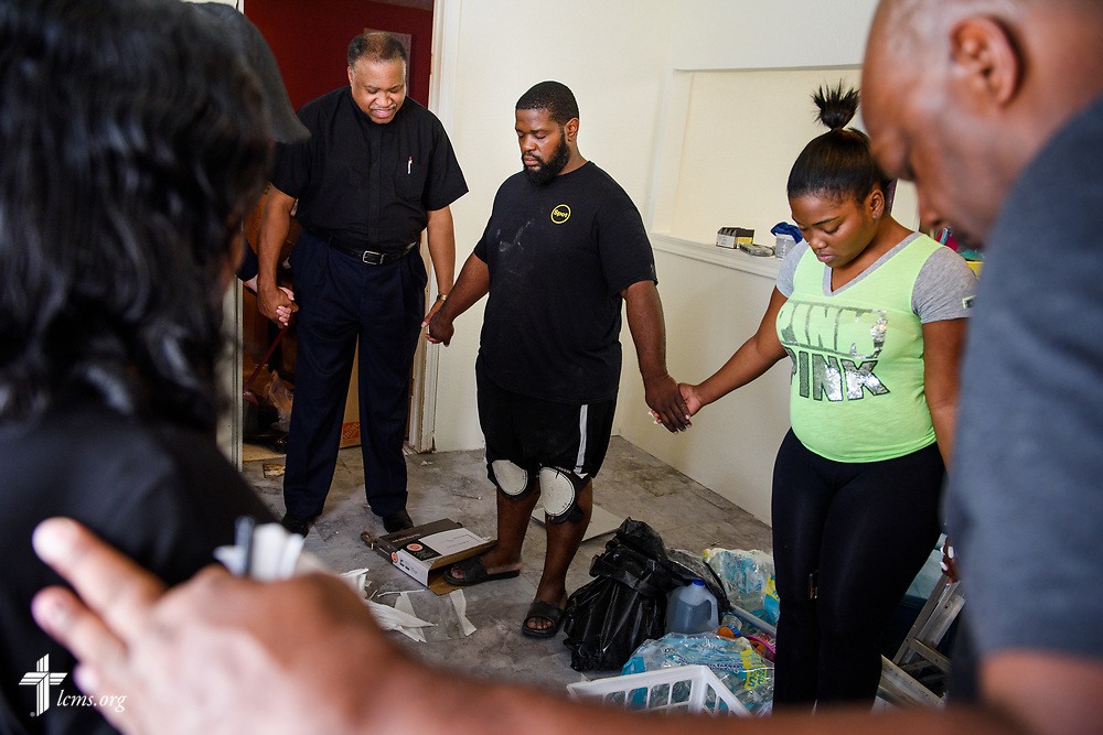 The Rev. Dr. Roosevelt Gray Jr., director of LCMS Black Ministry, joins other Synod leaders (not pictured) as he leads a family in prayer at their flood-damaged home on Tuesday, Sept. 26, 2017, in Houston. LCMS Communications/Erik M. Lunsford