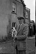 """Harry Walker, Kennelman, Westmeath Hounds, Mullingar.1962..05.02.1962..02.05.1962..5th February 1962..Picture shows noted kennelman Mr Harry Walker at his home at The Kennels, Knockdrin, Mullingar ,Co WestMeath. he is holding his own pet """"Judy""""."""
