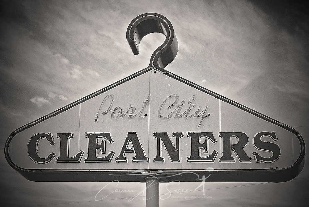 A sign shaped like a coat hanger advertises Port City Cleaners on Highway 90, July 10, 2016, in Mobile, Alabama. (Photo by Carmen K. Sisson/Cloudybright)