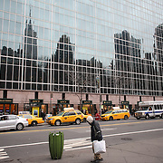 A sheet scene showing a reflection of New York's high rise buildings near Bryant Park, Manhattan, New York, USA.  Photo Tim Clayton