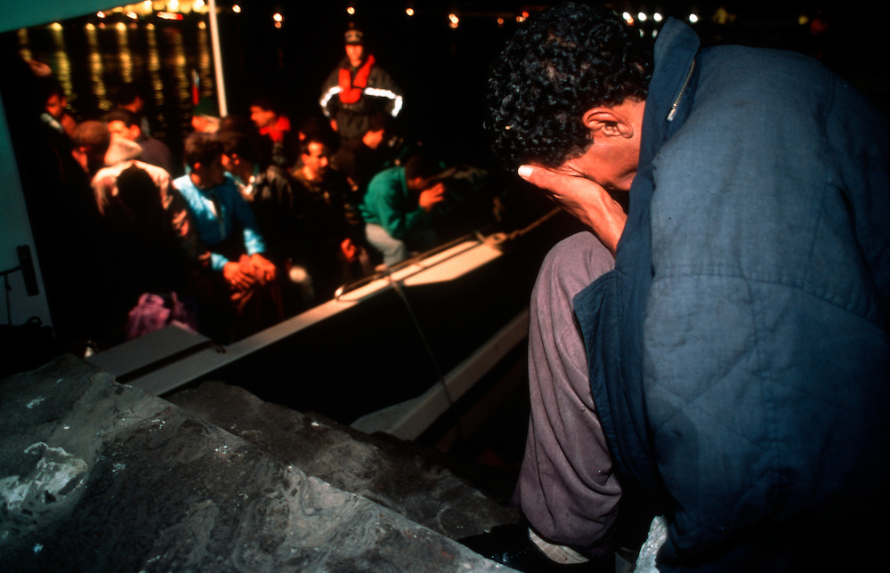 A boat load of illegal immigrants during a nocturnal attempt to enter Spain and the European Union by crossing of the Strait of Gibraltar from Morocco is stopped by a Spanish Guardia Civil patrol boat.<br /> Tarifa, Spain. October 1996.<br /> Photo &copy; J.B. Russell