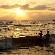 Children playing in the waves at sunset, Syria. Deux enfants jouent dans les vagues au soleil couchant, Syrie.
