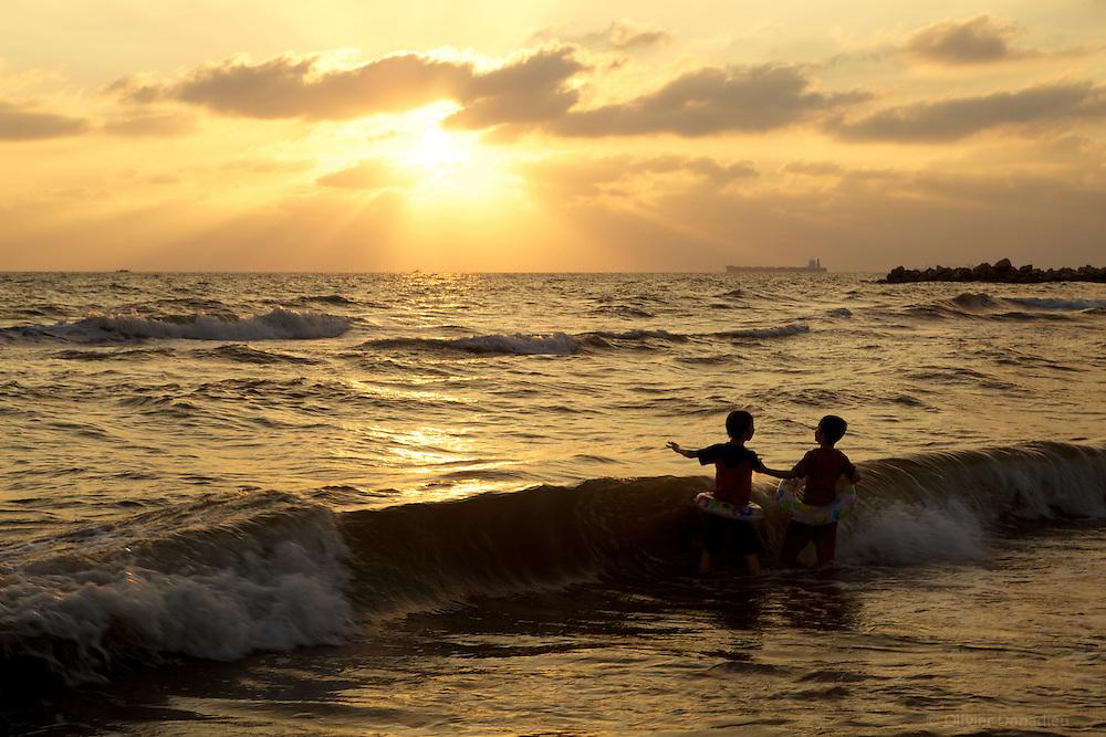 Children playing in the waves at sunset, Syria. Deux enfants jouent dans les vagues au soleil couchant, Syrie.