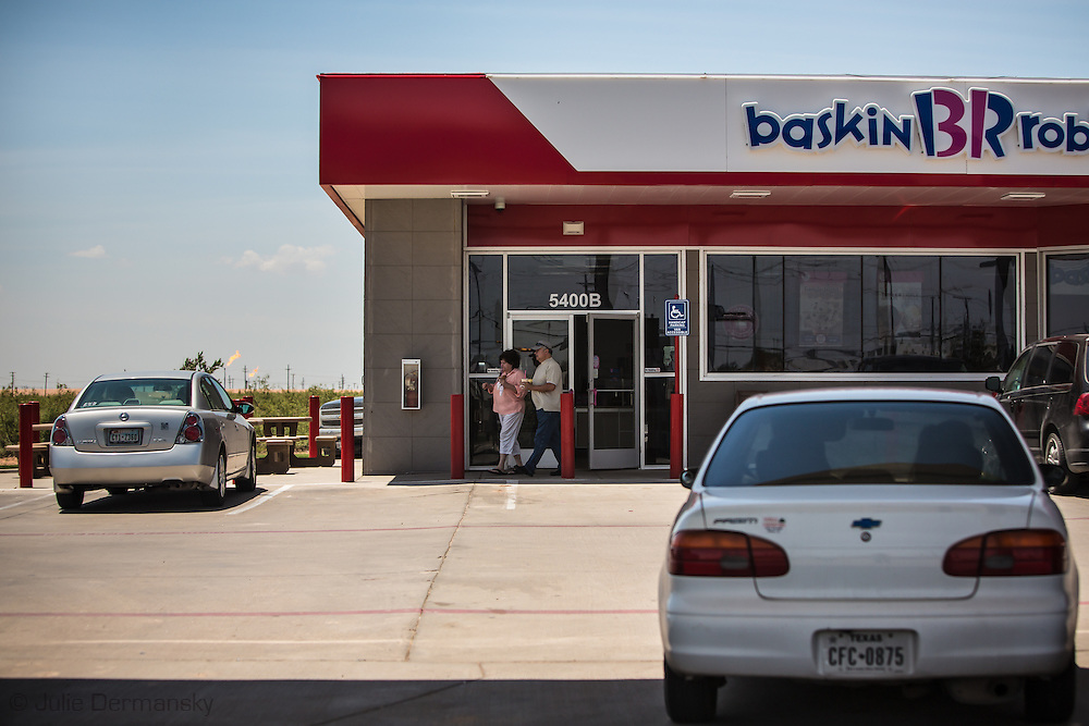 Flares burn at a fracking indsutry site behind a Chevron gas station with a Baskin Robbins Icescream shop connected to a convience store,  in Midland Texas in in the Permian Basin.