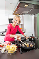 Portrait of smiling senior woman cooking food in kitchen