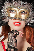 Young woman with feathered eye mask looking away