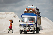 A woman walks on as a truck full of goods crosses salt dunes at the Lac Rose near Dakar, Senegal, on Tuesday, July 26, 2016. *** Second Sentence *** Photographer: Xaume Olleros/Bloomberg
