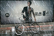 A bicycle covered in snow stands next to a Motorola advertisement at Olympic Square in Dalian, China on Saturday, Dec. 16, 2006.
