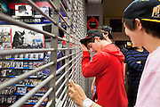 "24 NOVEMBER 2011 - PHOENIX, AZ:  Jack Nudo (CQ CENTER RED SHIRT), 17, and Drew Tsao, 17, (CQ RIGHT PINK SHIRT) both from Scottsdale wait for the Game Stop to open at Paradise Valley Mall Thursday. ""Black Friday,"" the unofficial start of the holiday shopping season started even earlier than normal. Many stores, including Target and Best Buy, opened at midnight.    Photo by Jack Kurtz"