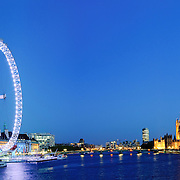 London's Millenium Wheel (London Eye) at left with the Houses of Parliament and Big Ben at right, looking down the Thames at night.