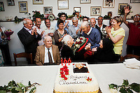 "PERDASDEFOGU, SARDINIA, ITALY - 30 JUNE 2013: Vittorio Palmas (99, turning 100 years old on December 16th) hands a bouquet a roses to Claudina Melis for her 100th birthday in Perdasdefogu, Italy, on June 30th 2013.<br /> <br /> Last year, the Melis family entered the Guinness Book of World Records for having the highest combined age of any nine living siblings on earth — today more than 825 years. The youngest sibling, Mafalda – the ""little one"" – is 79 years old.<br /> <br /> The Melis siblings were all born in Perdasdefogu to Francesco Melis and Eleonora Mameli, who had a general store. Consolata, 106, is the oldest, then Claudia, 100; Maria, 98; Antonino, 94; Concetta, 92; Adolfo, 90; Vitalio, 87; Fida Vitalia, 81; and Mafalda, the baby at 79. Their descendants now account for about a third of the village."