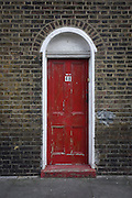 A poorly maintained red door with the number 48 of an old Victorian property in the north London district of Kings Cross. This area of north London is a across the road from the mainline station where European visitors arrive on the Eurostar from mainland Europe and the King Cross area is set for more redevelopment so the future for this original architecture is uncertain.