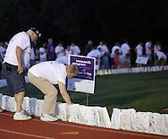 Goshen, New York - A woman lights a luminaria in remembrance of cancer victims during the Relay for Life at Goshen High School on June 19, 2011. The Relay for Life is the American Cancer Society's signature fundraising event. Participants celebrate the lives of people who have battled cancer, remember loved ones lost, and fight back against the disease by raising money.