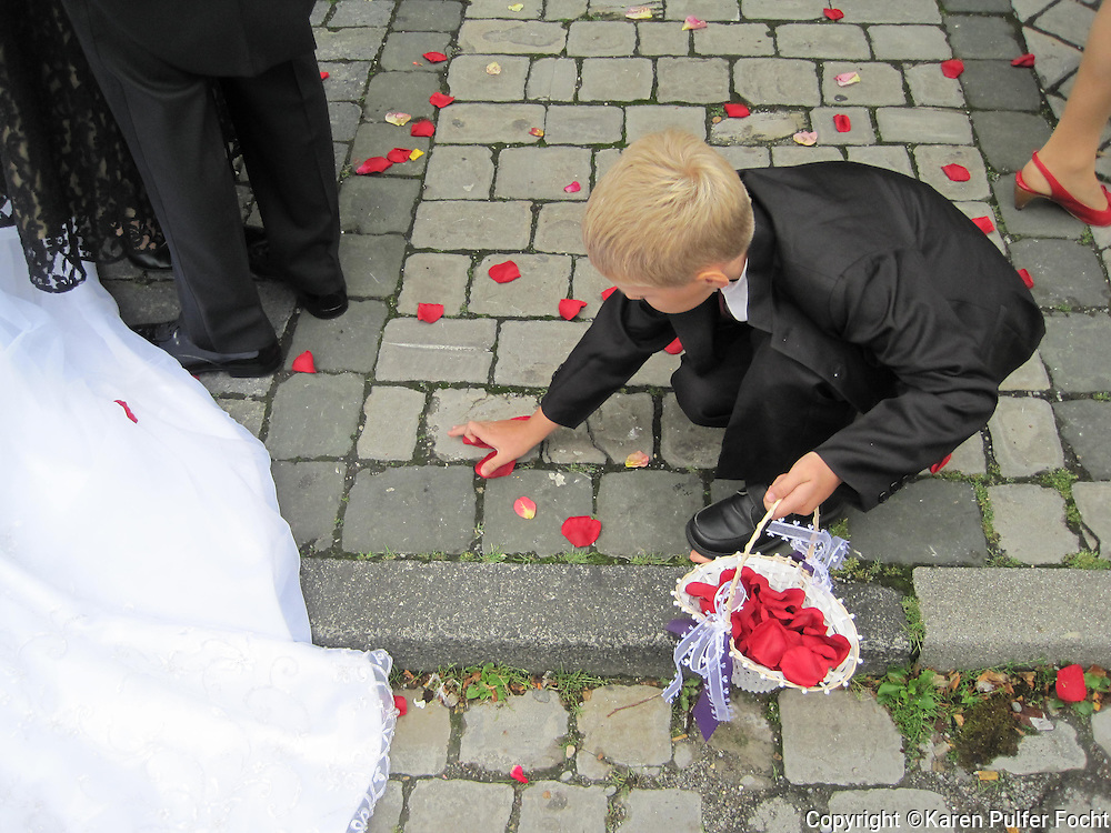 A young boy picks up flower petals following a wedding in Lindau, Germany.