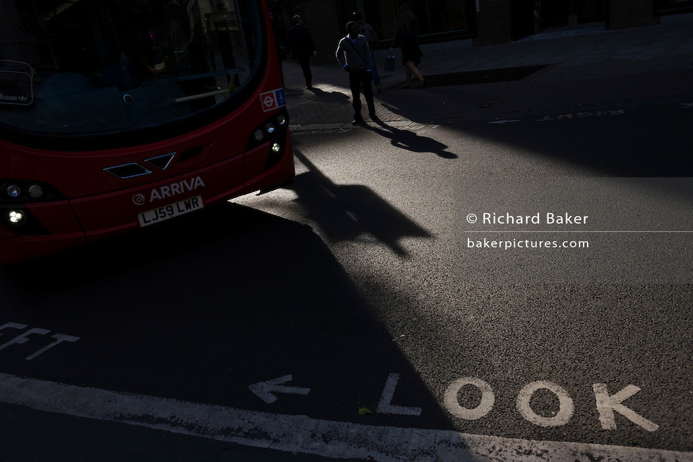 A Londoner looks the wrong way on a dangerous pedestrian crossing as a red bus turns across in central London.